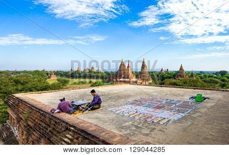 Bagan Myanmar - January 12 2012: Young people on a platform over the plain with thousand of 880-year old temple ruins.