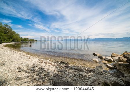 A beautiful rocky beach on lake Geneva near the city of Rolle canton of Vaud Switzerland.