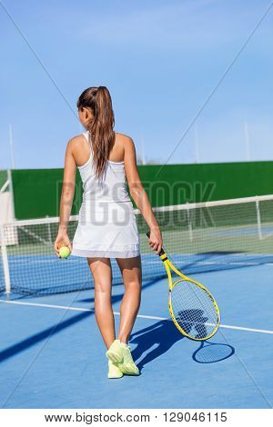 Tennis player woman in sportswear holding racket wearing white dress outfit and running shoes. Female athlete walking on outdoor court ready to play. fitness and weight loss concept. Summer hardcourt.