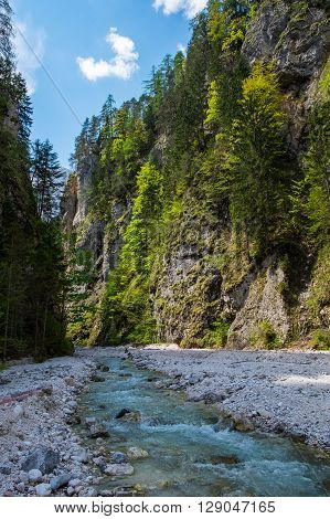 Mountain fast river stream in the rocks. Canyon with creek under blue sky. Pebble shore of brook.