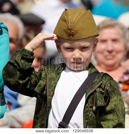 Orel Russia - May 9 2016: Celebration of 71th anniversary of the Victory Day (WWII). Little boy saluting in Russian military field cap closeup