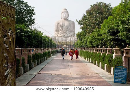 BODHGAYA, INDIA - JAN 8, 2013: Tourists walk past 24.38 metre Buddha statue on January 8 2013 in Bodhgaya India. Bodh Gaya is a place of pilgrimage. Siddhartha Gautama attained enlightenment here at 500 BC