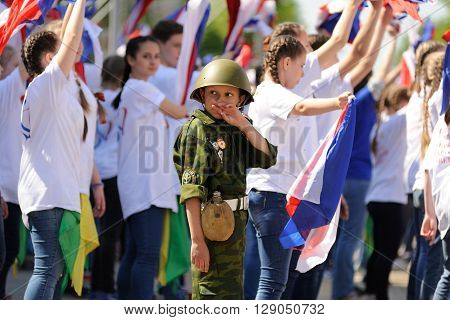 Orel Russia - May 9 2016: Celebration of 71th anniversary of the Victory Day (WWII). Boy in military uniform and helmet and young people dancing horizontal
