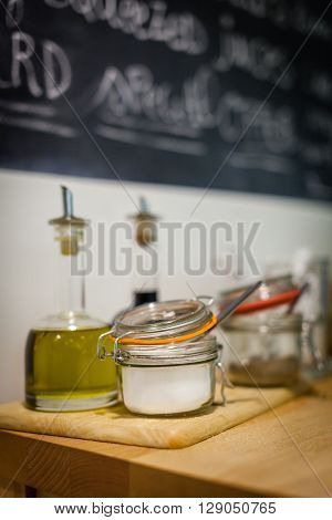 Table with condiments and additives like oil, vinegar, sugar, etc, in a student canteen