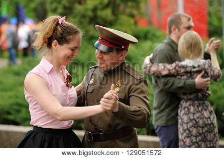 Orel Russia - May 9 2016: Celebration of 71th anniversary of the Victory Day (WWII). Man in military uniform dancing with woman in park horizontal