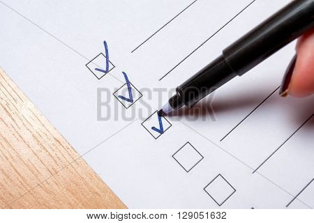 To do checklist on a light floor - girl ticking the box with a marker.