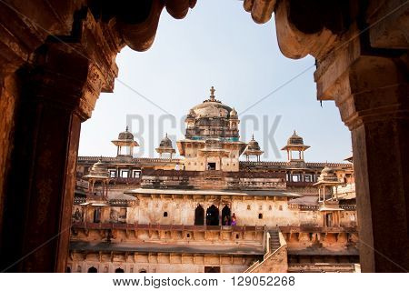 ORCHHA, INDIA - DEC 21, 2012: Historical arch with tourists walking in the fort Jahangir on December 21, 2012. Jahangir Mahal built in 1598. Its high position allowed Cannons to gain superior range