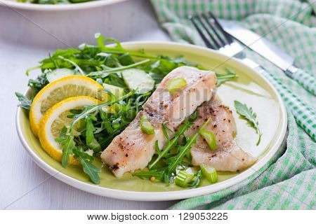 Steamed fish filet with green salad and lemon
