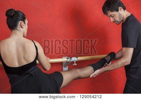 Trainer Assisting Female Ballet Dancer At Barre In Studio