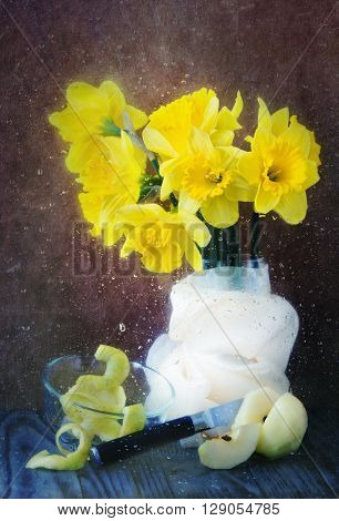 spring still life with daffodils and apple for a wet glass