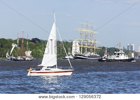 Hamburg, Germany - May 8, 2016: Participants in departure parade of 827th Hamburg Port Anniversary, among them Russian four-masted tall ship Kruzenstern. Small sail boat with spectators in foreground