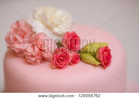 Close-up pink wedding cake with roses against  copy space background