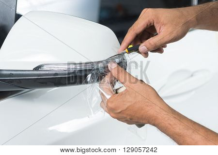 Paint protection film series : Cutting paint protection film on white car side mirror