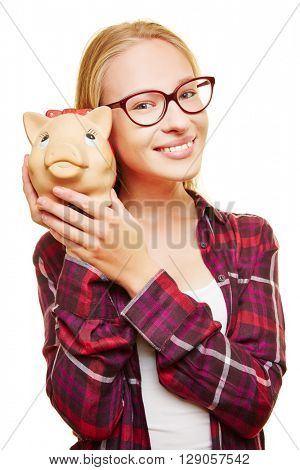 Smiling female teenager with glasses and a piggy bank in her hands