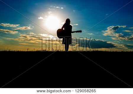 Silhouette Woman Playing Guitar In Sunset