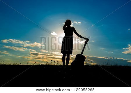Women With Guitar Over Sunset Sky,