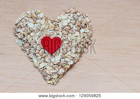 Dieting healthcare concept. Oat cereal heart shaped on wooden surface. Healthy food for lowering cholesterol protect heart.