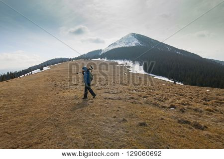 Lonely photographer in cold frosty mountains midday