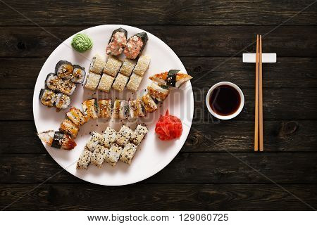 Japanese food restaurant, unagi sushi maki gunkan roll plate or platter set. Set for two with chopsticks, ginger, soy, wasabi. Sushi at rustic wood background. Top view, flat lay.
