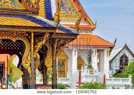 Details of Classical Thai architecture in National Museum of Bangkok Thailand. There is the Thai's Rama Statue in the background.