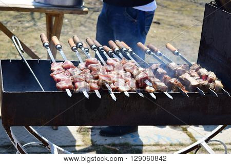 male fry meat on the grill, grill, nature, in the countryside, rest, smoke from the barbecue, delicious meat, roasted meat, meat on the grill
