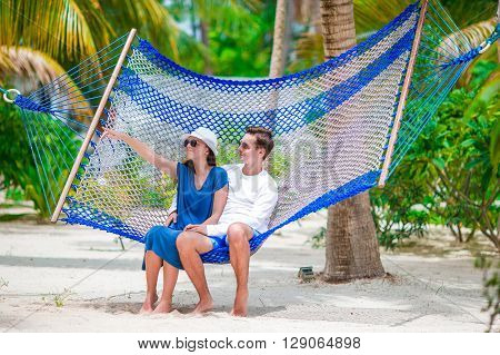 Young loving couple in a hammock in exotic resort