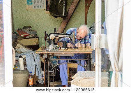 SARAJEVO BOSNIA AND HERZEGOVINA - SEPTEMBER 4 2009: Elderly man working on an old treadle sewing machine
