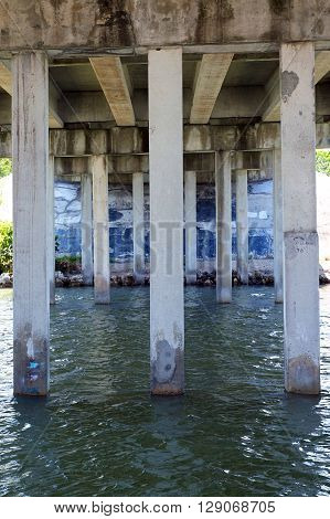 View from underneath concrete bridge of pylons and water moving south.