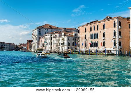 VENICE, ITALY - 17 OCTOBER 2015: Boat traffic in front of the Gritti Canal on the Grand Canal, Venice, Italy in a picturesque view looking up the canal at the historic architecture. October 17 2015.