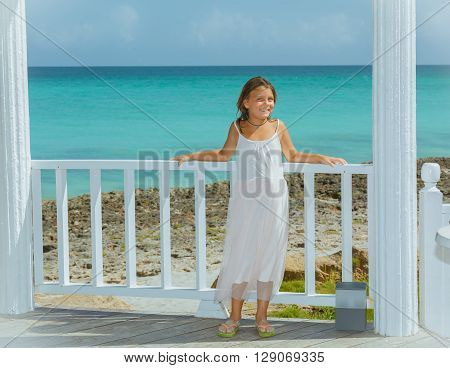 Joyful, happy little girl in white light dress leaning on gazebo wooden fence against the shore of the azure waters of Atlantic ocean background at sunny beautiful bright day