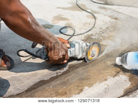 worker with cut-off machine power tool breaking asphalt at road construction site