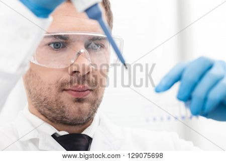 Skillful young researcher is dropping sample into the flask with inspiration. Man is standing and holding a pipette