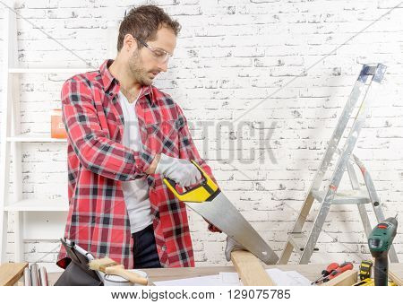 a smiling young man cutting a board with a hand saw