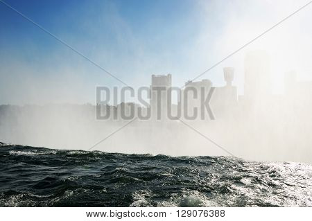 mist from Niagara Falls in the sky before city skyline