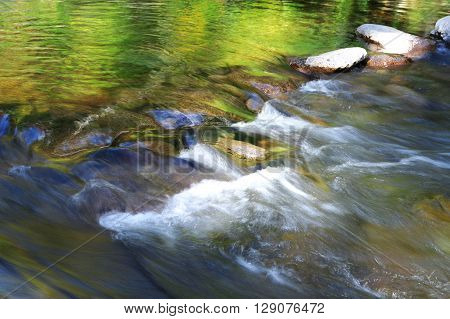 flowing water in brook reflecting green color