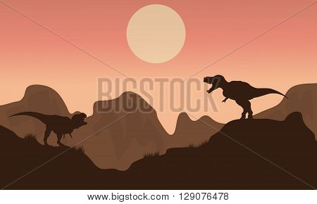 Silhouette of T-rex in cliff with sun at the morning