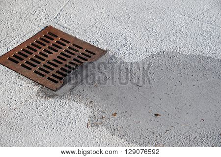 rustic square manhole drain cover in the street with water flowing in