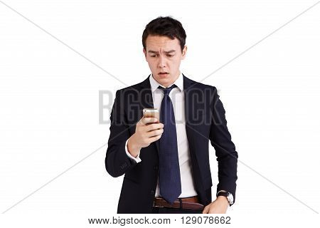 A young Caucasian business man is frowning holding a moble phone.