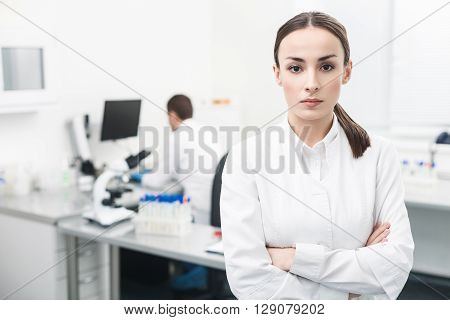 Attractive female scientist is standing in laboratory. She is looking at camera with seriousness. Her colleague is sitting at desk on background