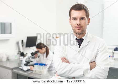 Waist up portrait of male doctor standing in lab. Man is looking at camera with confidence. His arms are crossed. Woman is sitting at desk and looking into microscope
