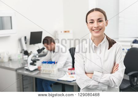 Waist up portrait of beautiful young scientist looking at camera with happiness. Woman is standing and smiling. Her colleague is sitting on background