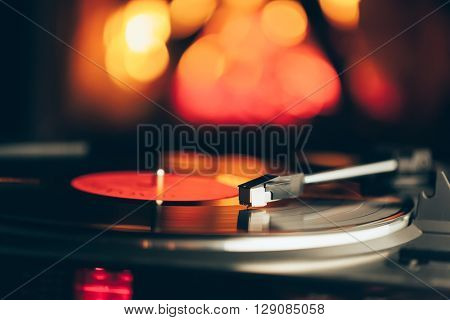 turntable with LP vinyl record against burning fire background