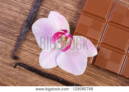 Portion of milk chocolate fresh fragrant vanilla sticks pods and blooming orchid flower on wooden background