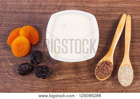 Portion of dried fruits oat bran and linseed with yogurt in bowl on wooden background concept of increase metabolism