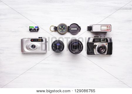 Top View Of Vintage Cameras On A White Wooden Background