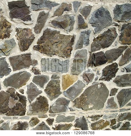 Stone wall made of different shaped stones. Realistic texture background, natural stones