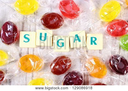 Heap of colorful candies with text sugar on old wooden background too many sweets unhealthy food and reduction of eating sweets