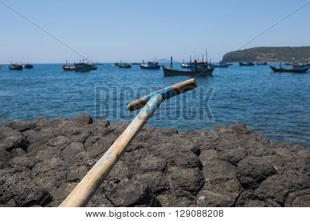Close up of a part of a paddle on background of many fishing boats anchoring at a harbor in Asia