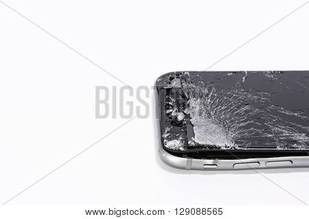 a mobile phone with cracked screen on a white background