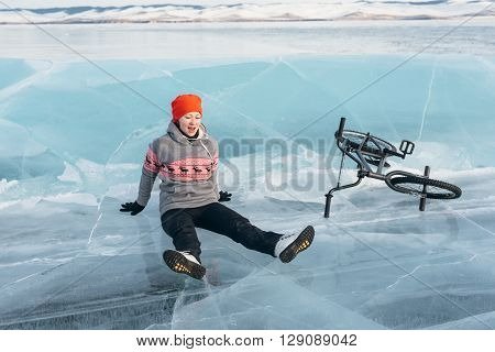 The girl fell from bmx on the beautiful and dangerous ice and rolled down.
